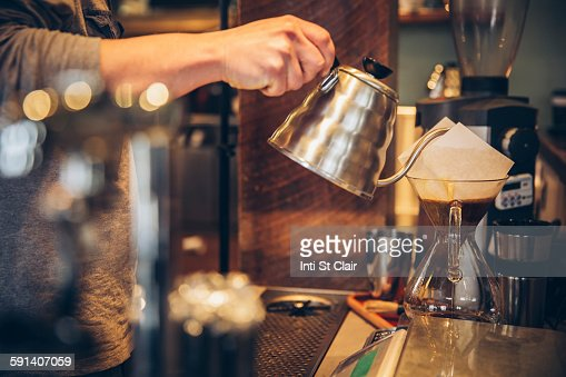 Caucasian barista pouring hot water over coffee in cafe : Stock Photo