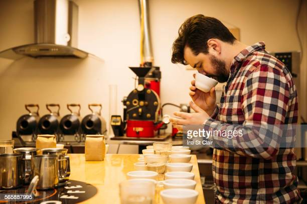 Caucasian barista tasting coffee in coffee shop