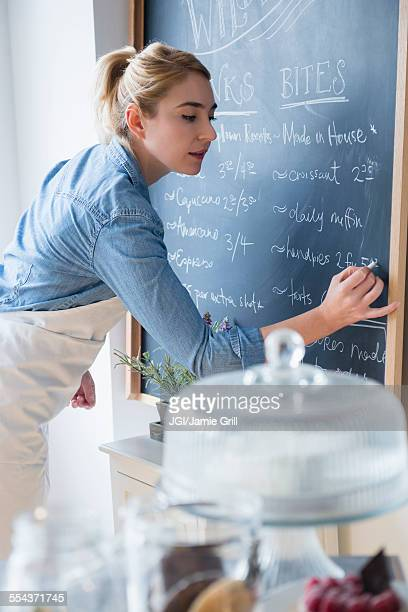 Caucasian barista writing menu on cafe chalkboard