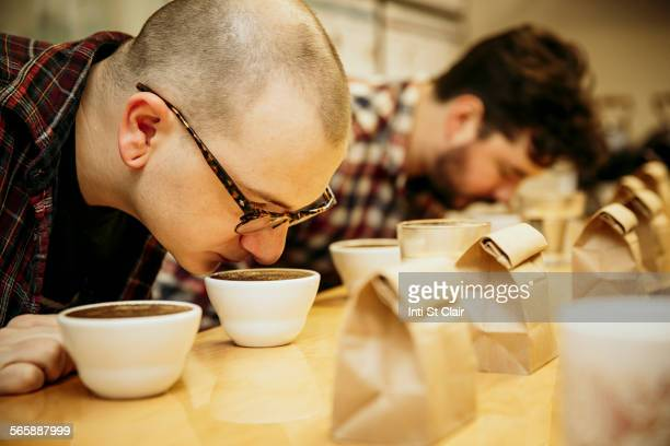Caucasian baristas smelling coffee in cups