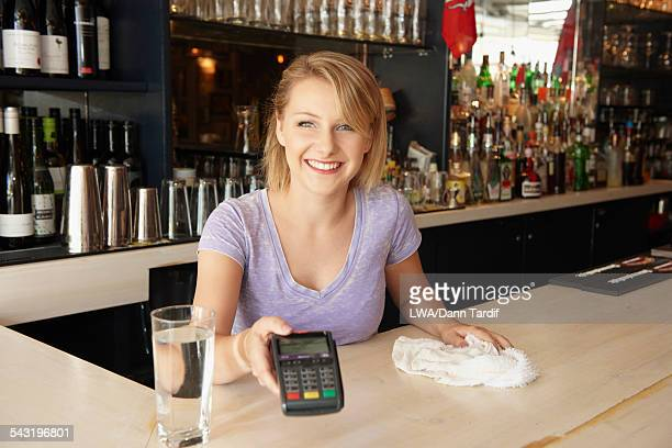 Caucasian bartender holding credit card reader in bar