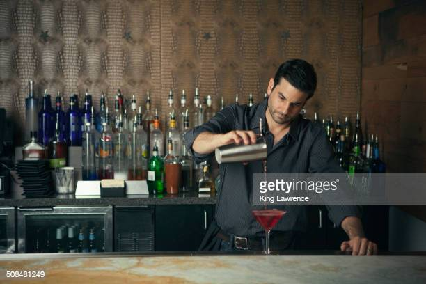 Caucasian bartender pouring drinks at bar