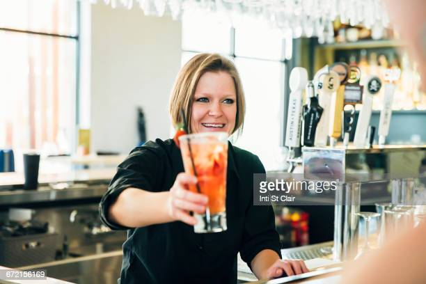 Caucasian bartender serving cocktail