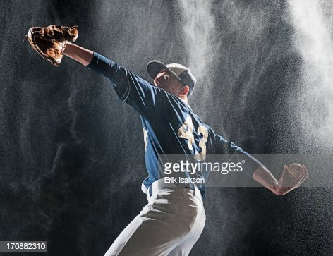 Caucasian baseball player pitching in rain