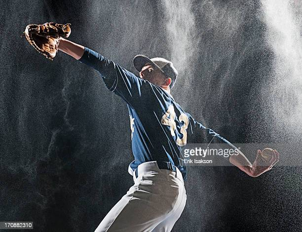 Caucasian baseball player pitching in rain