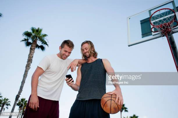 Caucasian basketball players looking at cell phone