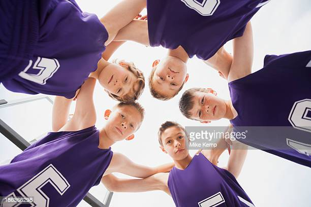 Caucasian basketball team in huddle