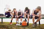 Caucasian basketball team sulking by court