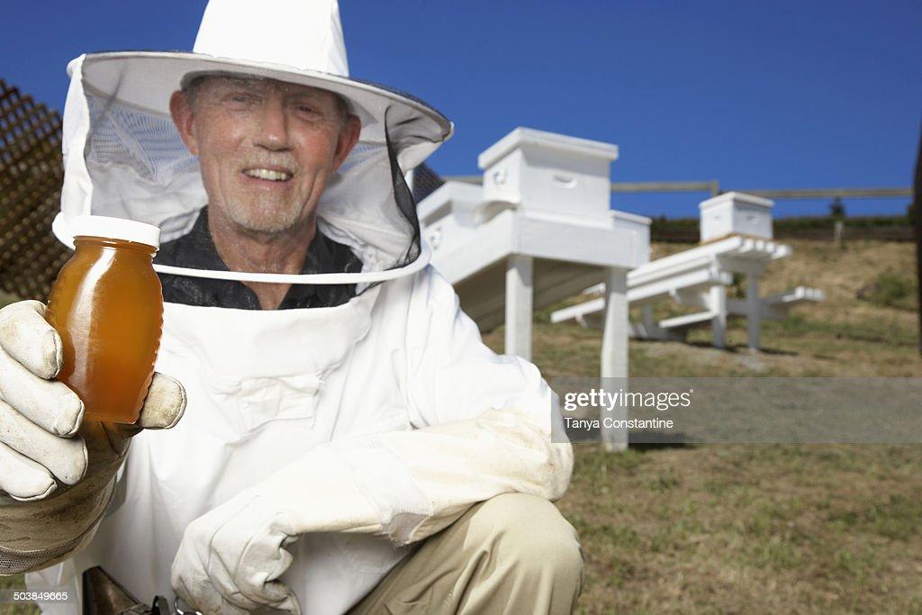 Caucasian beekeeper holding jar of honey