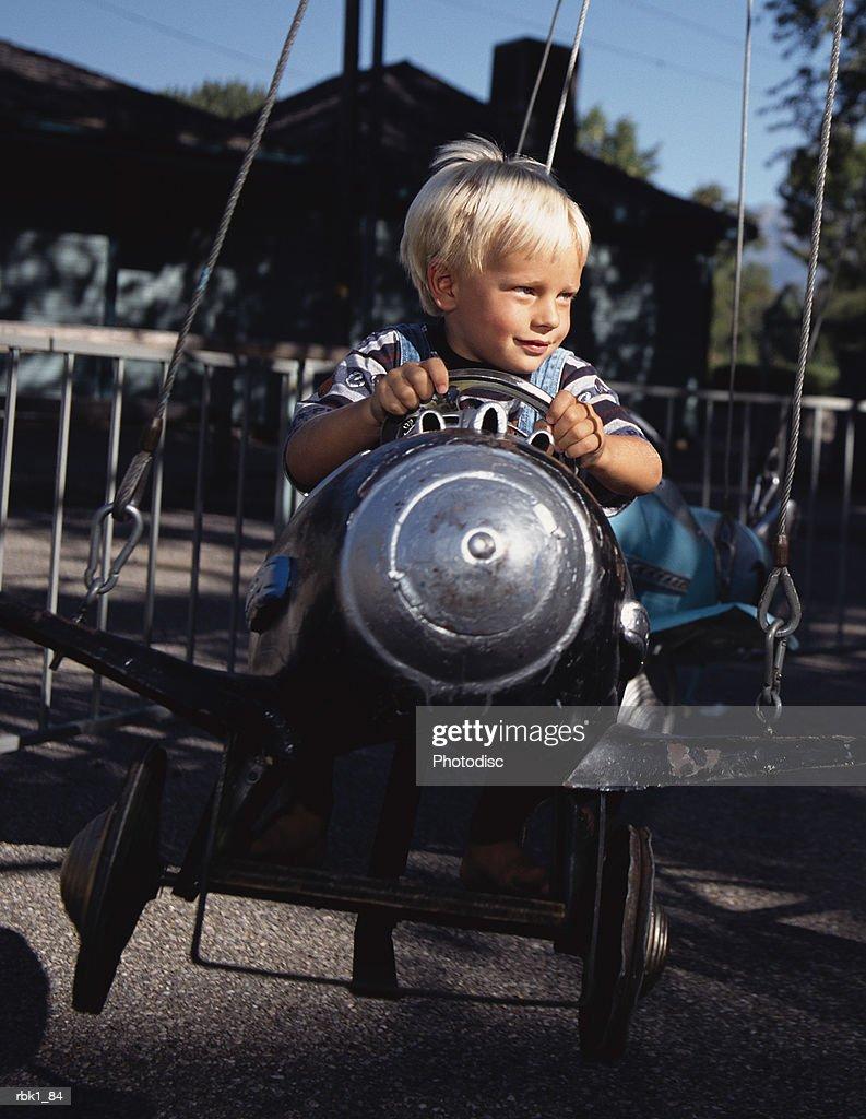 A caucasian blonde boy enjoys a plane ride at a park : Stock Photo