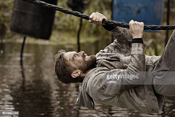 Caucasian blonde handsome man climbing obstacle during a mud run