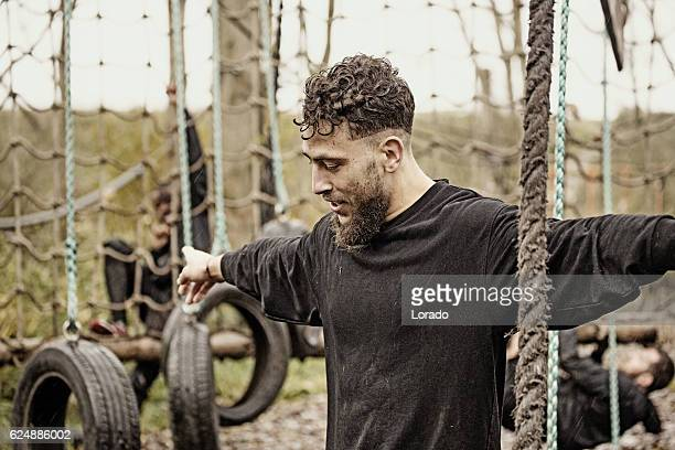 Caucasian blonde handsome young man climbing obstacle during mud run