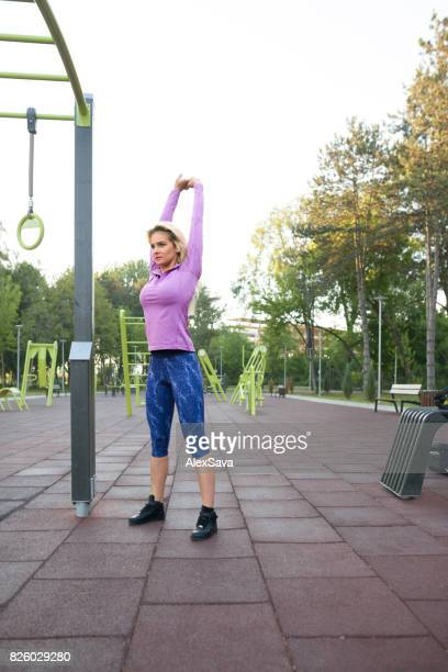 Caucasian blonde woman stretching before workout outdoor in the park