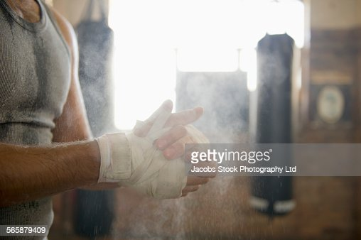Caucasian boxer chalking hands in gymnasium