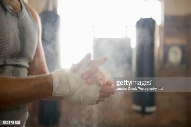 Caucasian boxer chalking hands in gymnasium