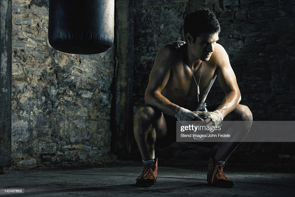 Caucasian boxer drinking water after training : Stock Photo