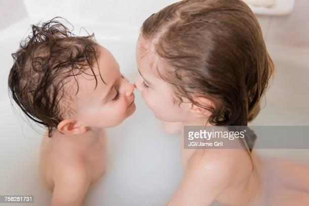 Caucasian boy and girl rubbing noses in bathtub