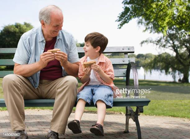 Caucasian boy and grandfather eating in park
