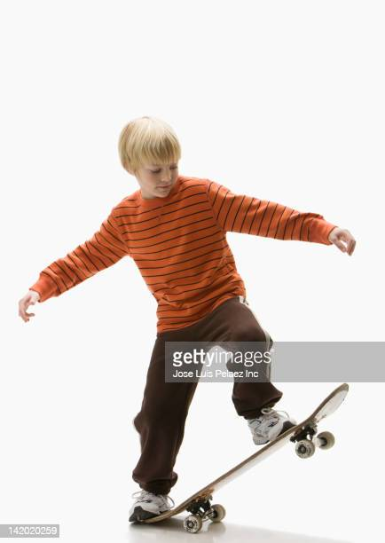 Caucasian boy balancing on skateboard
