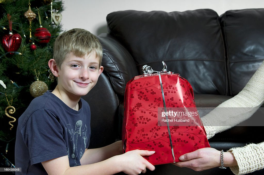 Caucasian boy being given a Christmas present : Stock Photo