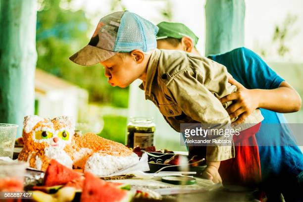 Caucasian boy blowing out candles on birthday cake
