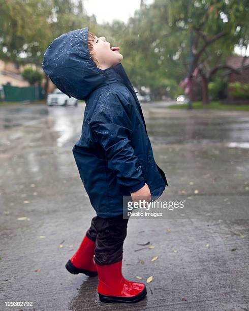 Caucasian boy catching raindrops on tongue