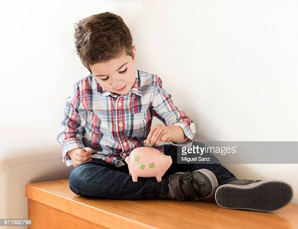 Caucasian boy depositing coin in piggy bank