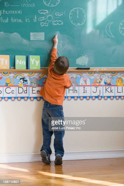 Caucasian boy drawing on blackboard in classroom