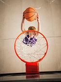 Caucasian boy dunking basketball in hoop