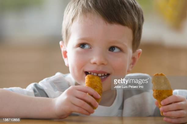 Caucasian boy eating chicken nuggets