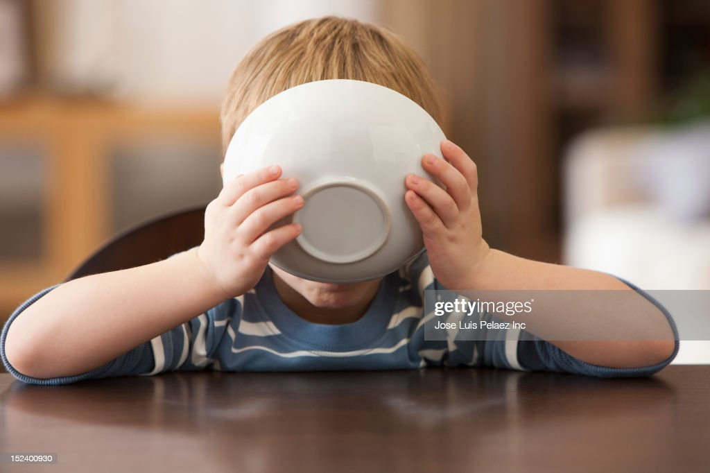 Caucasian boy eating from bowl : Stock Photo