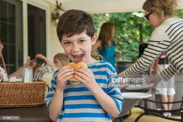 Caucasian boy eating hamburger on porch