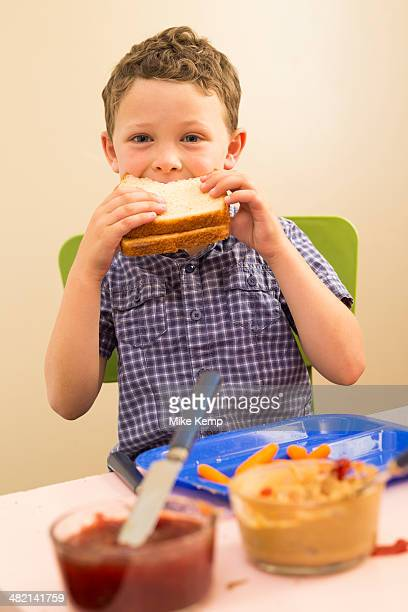 Caucasian boy eating sandwich in kitchen