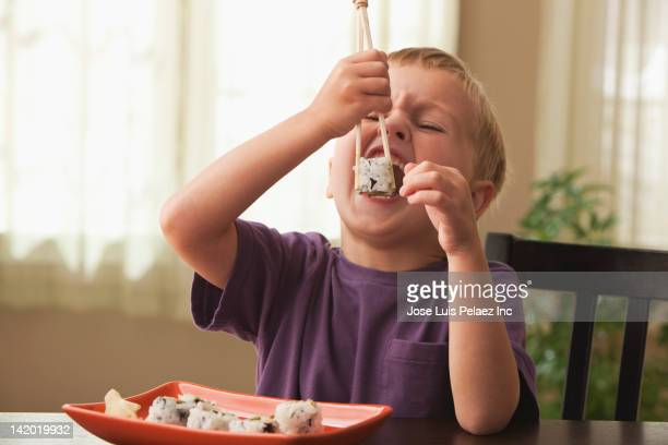 Caucasian boy eating sushi