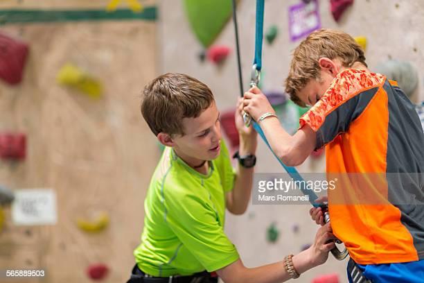 Caucasian boy fastening harness of boy near rock wall