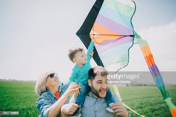 Caucasian boy flying kite with father and grandmother