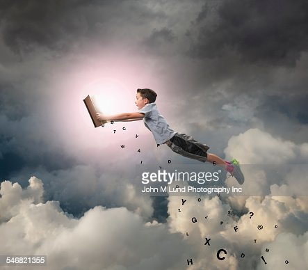 Caucasian boy flying with book in sky