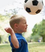Caucasian boy heading soccer ball