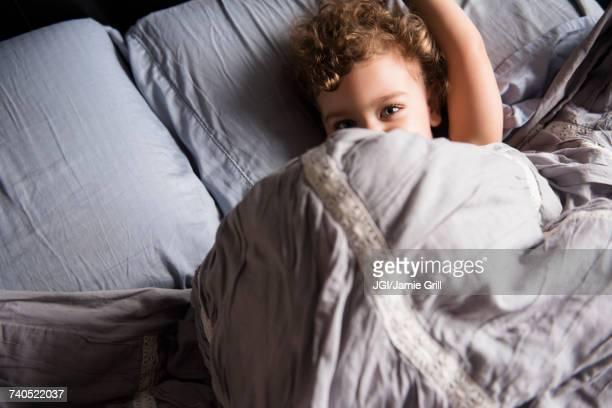 Caucasian boy hiding under blanket in bed