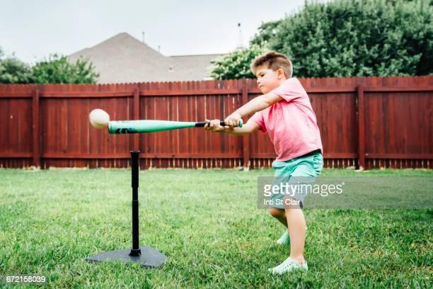 Caucasian boy hitting baseball off tee in backyard