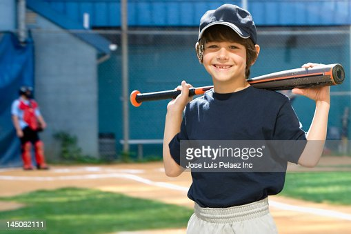 Caucasian boy holding baseball bat on field : Stock Photo