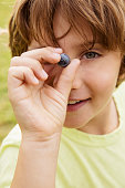 Caucasian boy holding blueberry outdoors