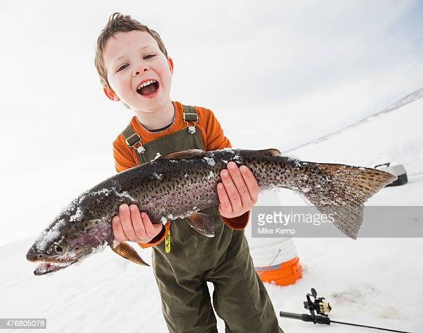 Caucasian boy holding fish in snow