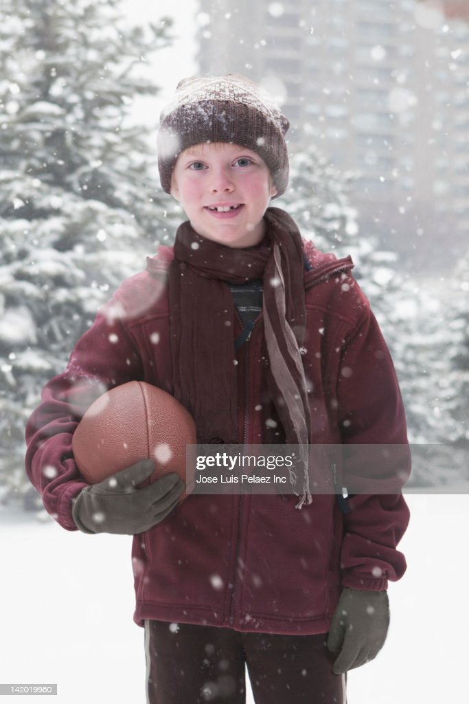 Caucasian boy holding football in the snow : Stock Photo
