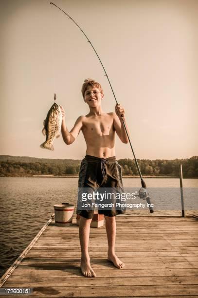 Caucasian boy holding freshly caught fish