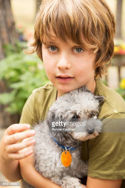 Caucasian boy holding puppy