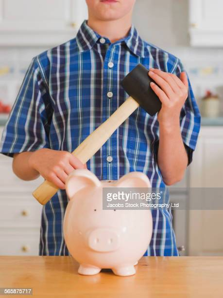 Caucasian boy holding sledgehammer over piggy bank