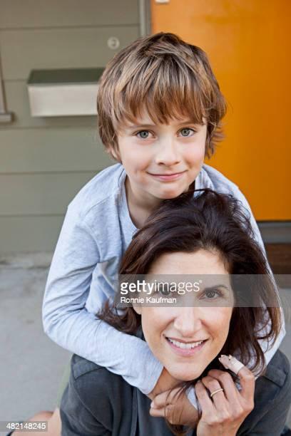 Caucasian boy hugging mother