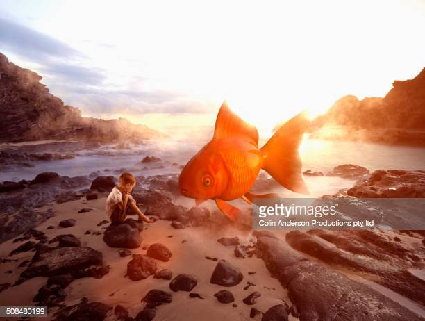 Caucasian boy imagining oversized goldfish on beach