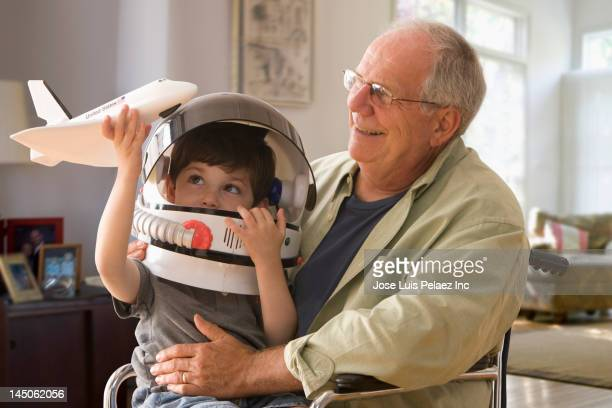 Caucasian boy in space helmet sitting on grandfather's lap